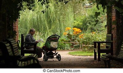 Calm old man reading newspaper sitting on bench near baby carriage