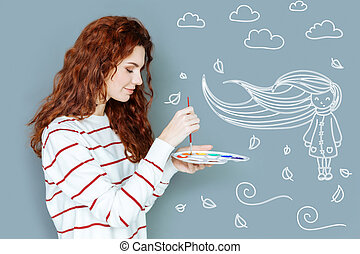 Calm painter holding a color palette and looking glad