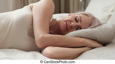 Calm peaceful happy adult older woman sleeping at home. - ...