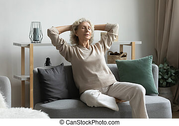 Calm peaceful middle aged mature hoary woman relaxing on cozy couch.