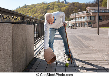 Calm pensioner dropping bag with products on the street
