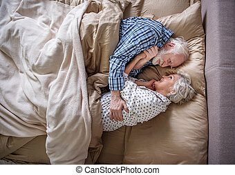 Calm pensioners embracing and lying in bed