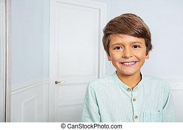 Calm positive portrait of little boy at home smile