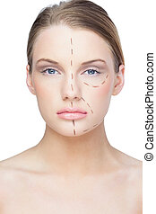 Calm pretty blonde with dotted lines on the face before surgery