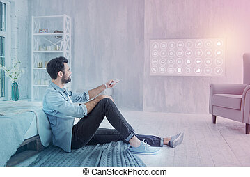 Calm programmer using remote control while sitting at home
