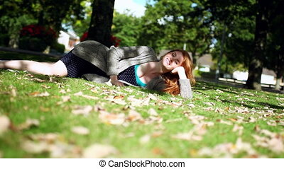 Calm redhead posing lying on green lawn wearing a...