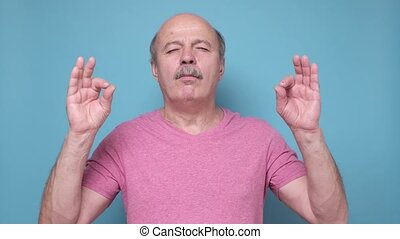 calm relaxed senior man showing om gesture meditating isolated on blue wall