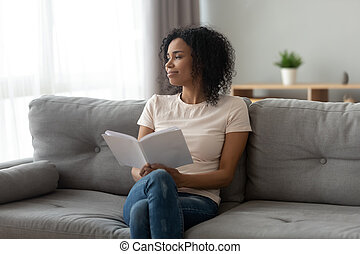 Calm satisfied African American woman relaxing at home, holding book