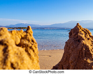Calm sea and a empty beach - small sandcastles in the front