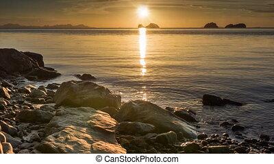 Calm sea at sunset rocks beach