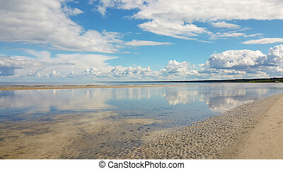 Calm sea on a sunny summer day. Reflected clouds in water