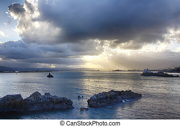 calm sea rocks in a sunset cloud