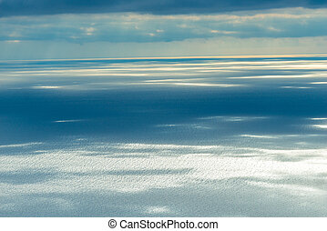 Calm sea surface in the rays of the sun breaking through the clouds