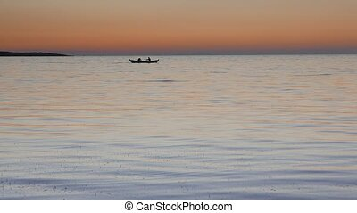 Calm sea with a rowing boat with two fishermen at sunset. 4k