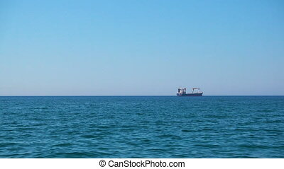 Calm sea with clear blue sky and cargo ship on the horizon