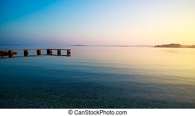 Calm Seascape. Pier and Sea at Sunset in Summer.