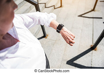 Calm senior lady noting time before coming down steps outdoors