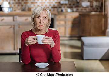 Calm senior woman sitting with a cup of tea