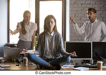 Calm serene employee meditating in office ignoring annoying coll