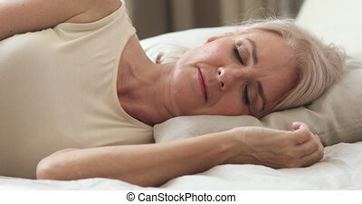 Calm serene healthy mature middle aged woman resting alone sleeping well in comfortable bed lying asleep on soft pillow relax on orthopedic mattress enjoy good night sleep concept, close up view