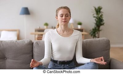 Calm serene woman sitting on couch meditating at home - Calm...