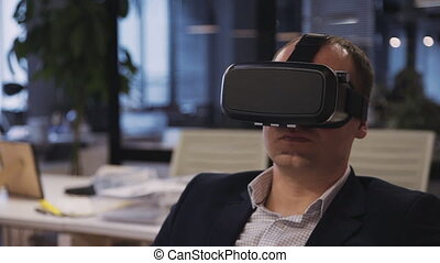 Calm, serious and confident mature man sitting behind his table in modern work space office with loft interior. Male wearing in 3d helmet or glasses and working in cyber space program
