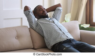 Calm carefree smiling african ethnicity young man relaxing on cozy sofa with closed eyes alone at home. Happy peaceful mixed race enjoying leisure time, daydreaming, meditating, breathing fresh air.