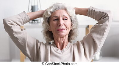 Calm smiling 70 years old woman relaxing at home. Serene senior lady enjoys peace comfort meditating holding hands behind head in living room. Happy granny feels relaxed breathing fresh air concept