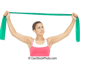 Calm sporty brunette stretching with resistance band on...