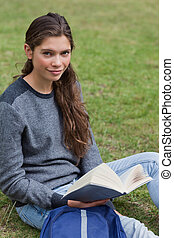 Calm student holding a book while sitting next to her backpack
