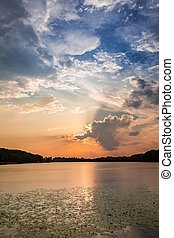 Calm sunset at the summer lake with dynamic clouds