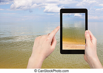 calm surface of Azov Sea on tablet pc - travel concept -...
