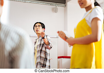 Calm teacher pointing to the speaker while conducting seminar