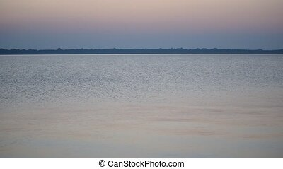 Calm water surface of a lake or river at dusk with colorful...