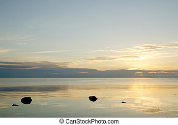 Calm water with black rocks in sunset