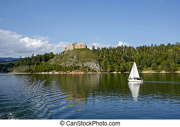 calm waters of the Czorsztyn Lake, yacht and ruins of ...