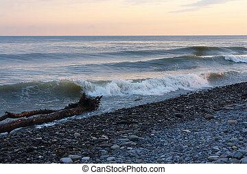 Calm waves on beach against the evening sky