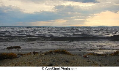 Calm waves on lake in the light of sunset
