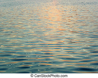 Picture of calm waves with a sunset color sparkle.