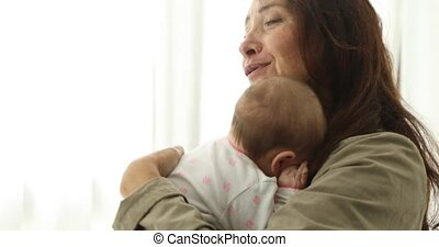 Calm woman embracing and kissing newborn baby