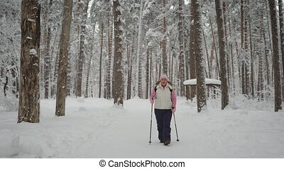 Calm woman goes in for sports in the winter cold forest. She warmly dressed in sportswear. is energetically along the path past the tall pines, singing a song