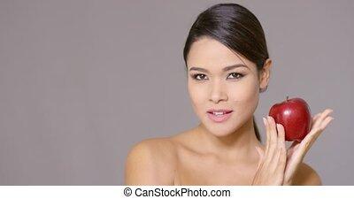 Calm woman holding an apple near her cheek - Single calm...