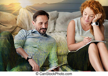 Calm woman making notes while her boyfriend sitting near and reading