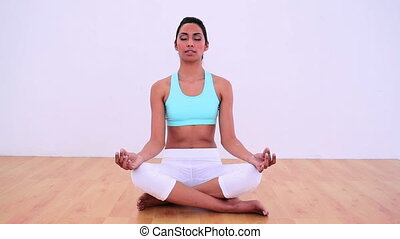 Calm woman meditating in lotus posi