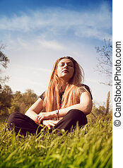 Calm woman relaxing in sunny grass field