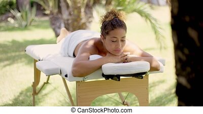 Calm woman relaxing on massage table outside - Calm grinning...