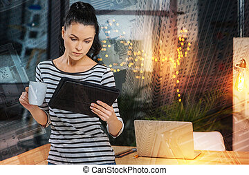 Calm woman standing with a tablet while drinking coffee