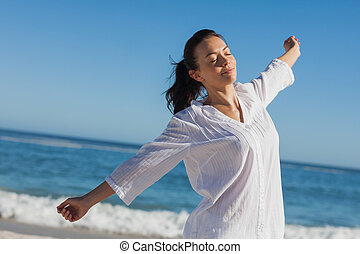 Calm woman stretching at beach on a sunny day