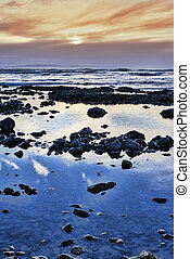 calm yellow sunset over rocky beach