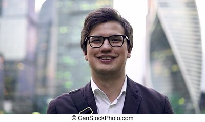 Calm young businessman portrait, smiling to the camera in a big city, summer